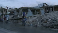 January 8 2011 WS Light traffic and residents walking on the streets next to destroyed homes and rubble / PortauPrince Haiti
