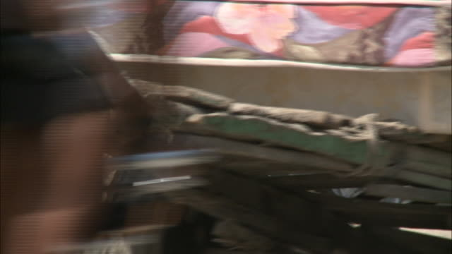 January 8 2011 TS Villager pulling a handcart loaded with a fullsized mattress across a busy street / Leogane Haiti