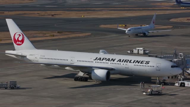 A Japan Airlines Corp aircraft taxis past a parked Japan Airlines Corp aircraft at Haneda Airport in Tokyo Japan on Tuesday Jan 26 Logo for Japan...