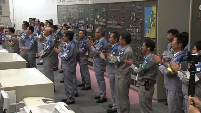 [Japan Out]Wide angle view Entire view of the Sendai nuclear power plant's central control room Two workers turning a lever to generate electricity...