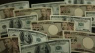 Japanese 10000 yen banknotes and US onehundred dollar banknotes stand up on a table worktop spotlight shining on a US onehundred dollar bill Japanese...