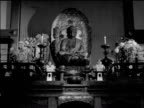 / Japanese Buddhist ceremony / ZOOM IN on altar statue of Buddha / CUs of altar statue candle Religious icons at Buddhist ceremony on January 01 1950...