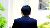 Japanese businessman turning and making ok sign