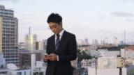 MS A Japanese businessmen sends a message on his phone with Tokyo in background / Tokyo, Japan