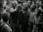 Japanese children gathered around United States soldier soldier spoon feeding boy reading comics w/ another boy Democratization