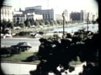 WS Japanese children in kimonos and young woman in dress near shoreline look, point and wave at commercial planes landing,  Tokyo street and Imperial Palace / Tokyo, Japan / AUDIO
