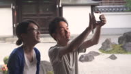 Japanese couple taking picture with smartphone