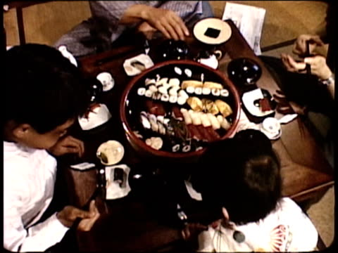 1963 MONTAGE Japanese family having traditional dinner together / Japan