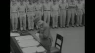 Japanese foreign minister Namoru Shigemitsu walks up to table on deck of ship / as he sits at table assistant shows him surrender documents / two...