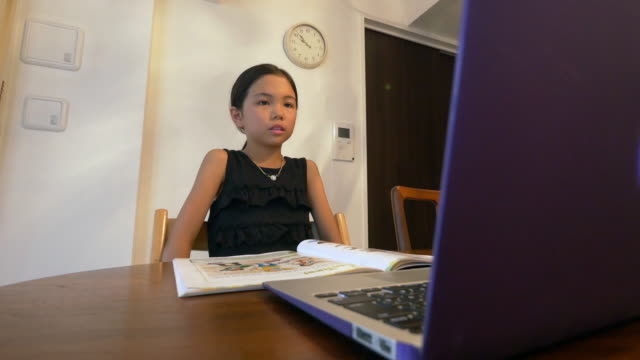 Japanese girl aged 9 years using laptop for online study English