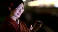Japanese Girl in a Kimono Texting at night in Shibuya