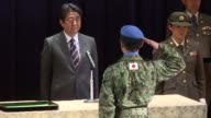 Japanese Prime Minister Shinzo Abe attends a ceremony at the Defence Ministry in Tokyo marking the return of the country's international peacekeeping...