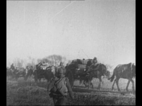 Japanese soldiers advance in flooded area in Manchuria / Japanese transport carts horses soldiers advance / montage Japanese soldiers march in...