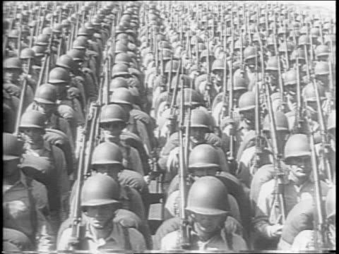Japanese soldiers raising hands / map of the United States superimposed over footage of American industrial work / US soldiers marching / four...