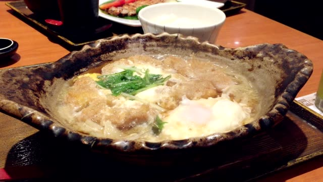 Japanese tonkatsu with onsen egg in Miso soup, hot pot on desk at restaurant.