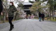 Japanese visitors walking up and down a paved trail at a garden with traditional architectural structure in the background