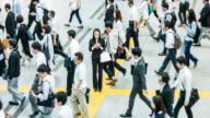 Giapponese donna parlando sul cellulare circondato da pendolari