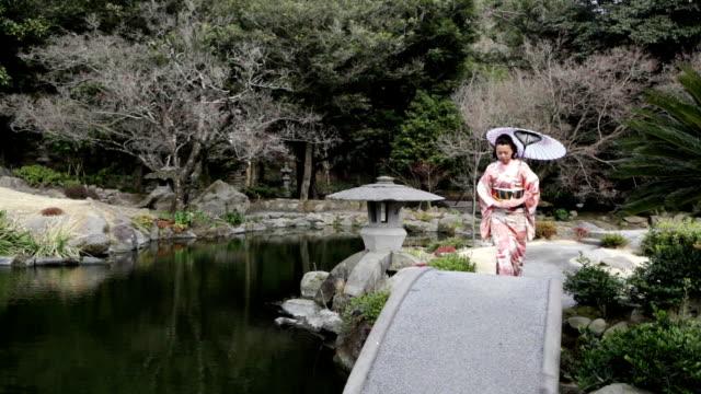 HD: Japanese woman walking in garden (video)