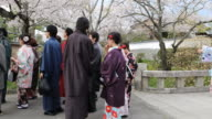 Japanese women in traditional attire walking down a concrete path at a city garden in Kyoto
