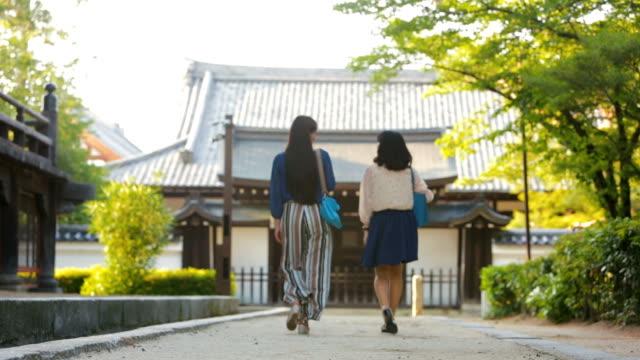 Japanische Frauen zu Fuß auf dem Gelände eines buddhistischen Tempels
