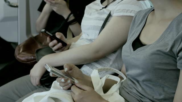 Japanische Junge Frauen mit smartphone auf dem Zug.