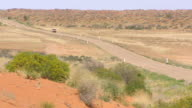 WS Jeep approaching on outback road with landscape / Boulia, Queensland, Australia