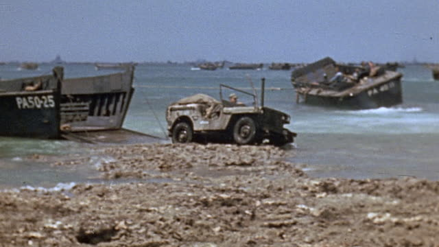 Jeep equipped with snorkel exiting landing craft and driving up the beach / Okinawa Japan