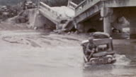 Jeep pulling loaded trailer crossing a river beside bomb damaged bridge and becoming stuck in the mud during WWII / Okinawa Japan