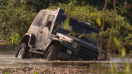 A Jeep spins its wheels in a muddy swamp.