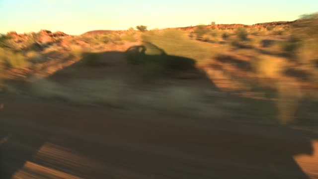 A Jeep's shadow speeds across a desert landscape. Available in HD.