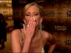 HANDHELD Jenna Jameson standing on carpet in Beverly Hilton hotel blowing kiss into camera winking