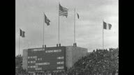 Jesse Owens runs down track and makes jump at 1936 Summer Olympics / stadium scoreboard with international flags above / women's 100meter dash...