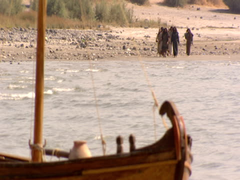 Jesus and his disciples walk along the shore of the Sea of Galilee.