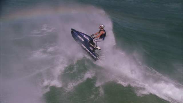 Jet skier ramps wave and performs trick mid-air before landing on water, Durban Available in HD.