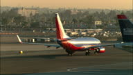 WS, Jet taxiing in runway, baggage truck crossing frame, Los Angeles, California, USA