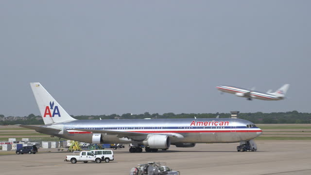 AA jetliner parked on tarmac with plane taking off in background/DFW International Airport, Dallas-Fort Worth, Texas, USA