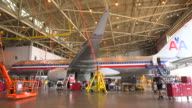WS AA jetliner (Boeing 757) serviced in hanger with worker pulling tool cart passing foreground/DFW International Airport, Dallas-Fort Worth, Texas, USA