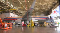 WS AA jetliner (Boeing 757) serviced in hanger with workers in cart passing foreground/DFW International Airport, Dallas-Fort Worth, Texas, USA