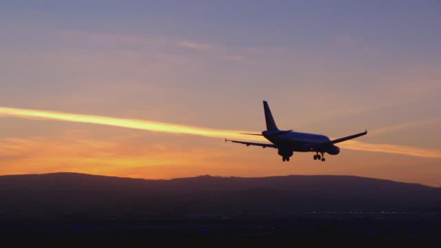 Jetliner streaks across sunset sky in silhouette on approach to landing
