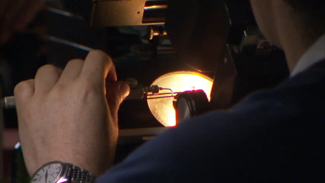 A jeweler adjusts a clamp under a bright light.