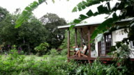 Jib crane shot of man and woman sitting on porch of cabana in lush jungle forest.