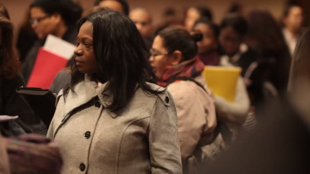 Job Fair in New York NY US on Thursday Jan 16 Close up a white midthirties female waiting on a line inside the job fair Close up a white male wearing...