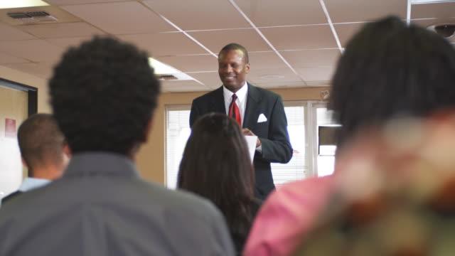 CU, SELECTIVE FOCUS, Job fair leader talking to group in unemployment office, Phoenix, Arizona, USA