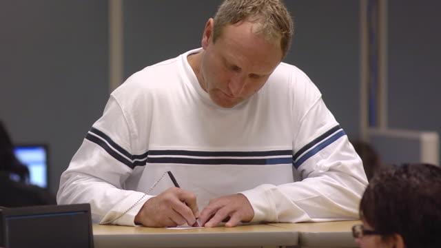MS Job seeker talking and writing on chit at counter of state run job center / Jackson, Michigan, United States
