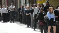 Job seekers wait on line to enter the Choice Career Fairs job fair outside the Holiday Inn Midtown in Manhattan New York Shots pan across a long line...
