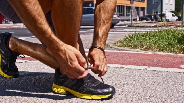SLO MO Jogger tying his shoes