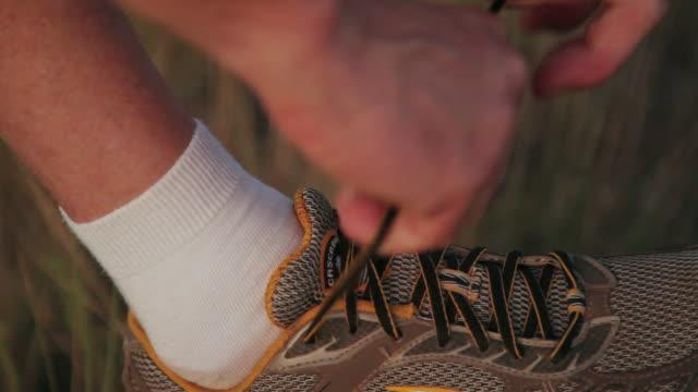 CU Jogger's hands tying his running shoe / Flagstaff, Arizona, USA