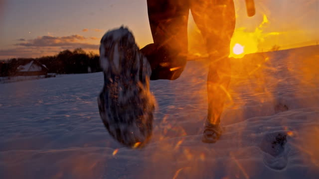 SLO MO Jogging Through The Snow At Sunset