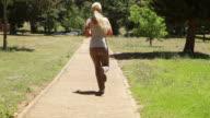 Jogging woman runs down the footpath