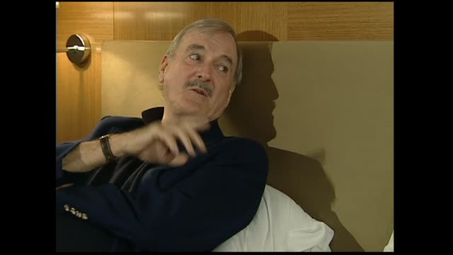 John Cleese interviewed on hotel bed in 2005 by host Susan Wood giving long winded answer to philosophy question concerning watching the cup final on...